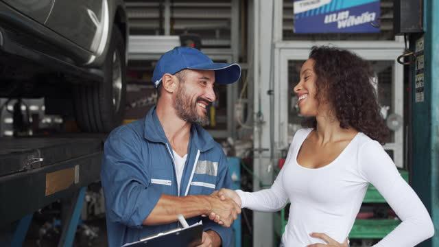 vídeos de stock e filmes b-roll de auto repairman  in auto repair shop with customers. - oficina