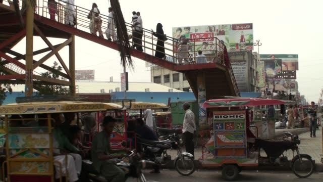 Auto Rickshaws pick up passenger beneath an overpass in Karachi Pakistan Motorized rickshaws wait for passengers while commuters sit on the rooftops...