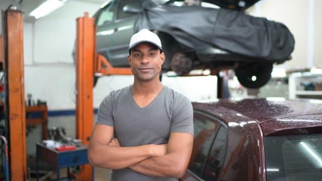 stockvideo's en b-roll-footage met auto service latin afro werknemer / eigenaar - armen over elkaar