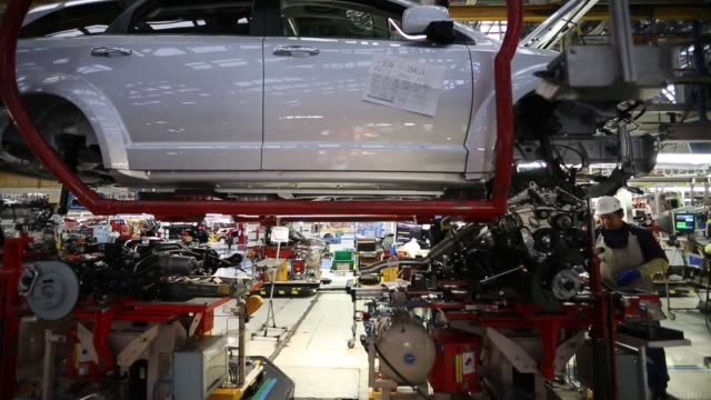 stockvideo's en b-roll-footage met auto workers assemble chrysler automobiles inside chrysler group llc's assembly plant in toluca mexico various large pieces come off the assembly... - chrysler