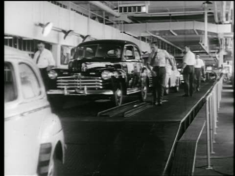 b/w 1945 auto workers inspect completed car in car assembly line / educational - production line stock videos & royalty-free footage