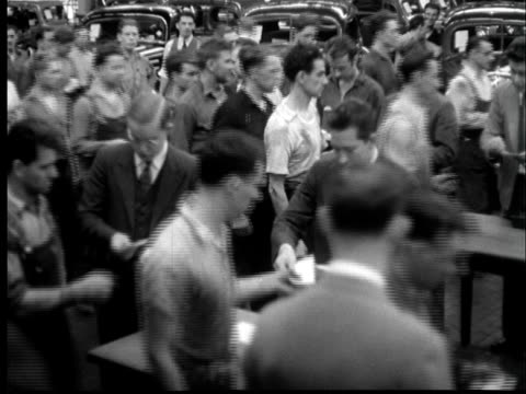 1937 film montage  ws auto workers receiving paychecks/ ms workers getting checks/ cu hands/ ms office workers receiving checks/ ws factory workers - 自動車産業点の映像素材/bロール