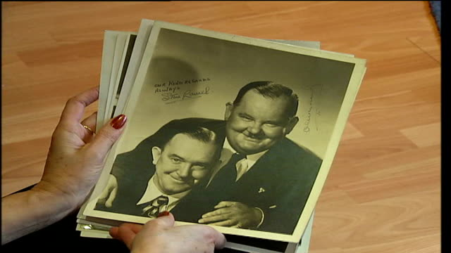 autograph collection owned by alan robinson up for auction high angle shot of reporter holding photographs **davie interview partly overlaid sot**... - autogramm stock-videos und b-roll-filmmaterial