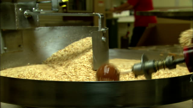 automated arms roll caramel apples across a vat of chopped nuts. - toffee stock videos & royalty-free footage