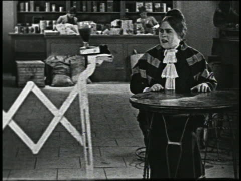 b/w 1926 automated drink maker serving glass to woman seated in soda fountain / short - 1926 stock-videos und b-roll-filmmaterial
