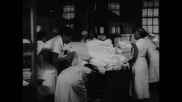 vidéos et rushes de automated empty glass bottles moving being filled w/ liquid bg dominican laundry workers standing next to table w/ folded sheets women seated - antilles occidentales