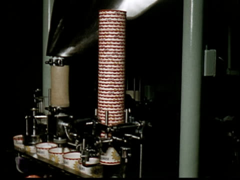 vidéos et rushes de 1955 ms automated machine filling and sealing borden's containers with cottage cheese/ containers moving on conveyor/ worker's arms picking up containers - salle de traite