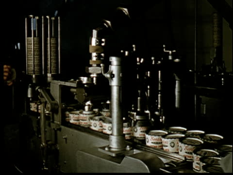 vidéos et rushes de 1955 film montage ms automated machine filling and sealing containers of borden's cottage cheese / ms containers on conveyor / ms pan machine filling and sealing containers/ ms hands of worker boxing the finished product - salle de traite