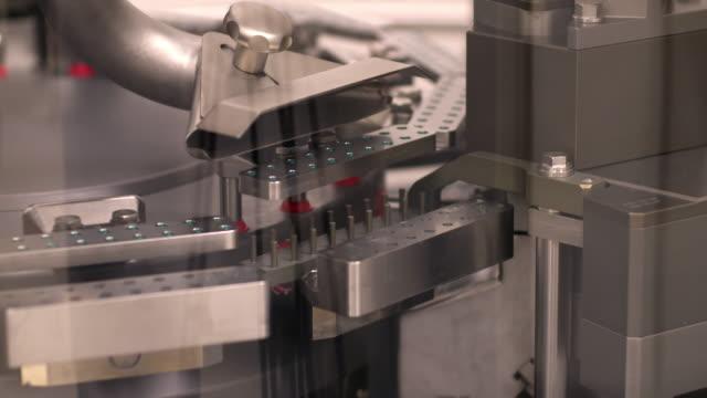 automated machine preparing medicine capsules - läkemedelsfabrik bildbanksvideor och videomaterial från bakom kulisserna