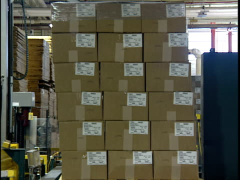 ms automated packing machine wrapping stack of cardboard boxes in distribution warehouse / new jersey, usa - 梱包機点の映像素材/bロール