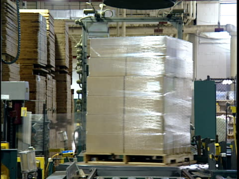MS Automated packing machine wrapping stack of cardboard boxes in distribution warehouse / New Jersey, USA