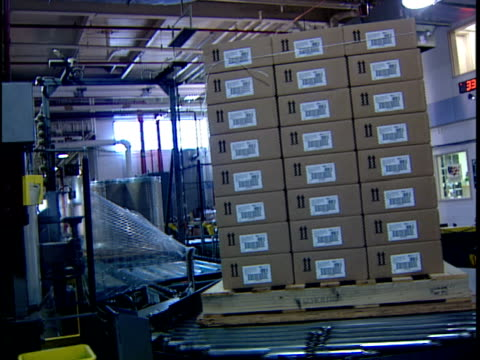 ws zi automated packing machine wrapping stack of cardboard boxes in distribution warehouse / new jersey, usa - 梱包機点の映像素材/bロール