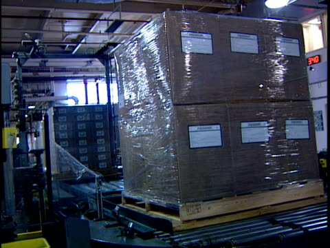 ws automated packing machine wrapping stack of cardboard boxes in distribution warehouse / new jersey, usa - 梱包機点の映像素材/bロール