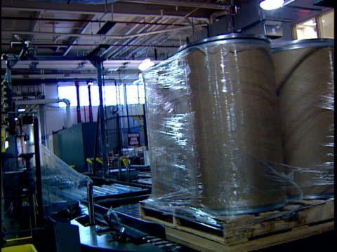 ws zi automated packing machine wrapping stack of cardboard cylinders in distribution warehouse / new jersey, usa - 梱包機点の映像素材/bロール