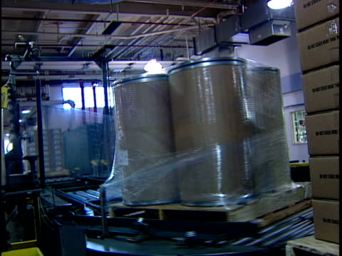 ws automated packing machine wrapping stack of cardboard cylinders in distribution warehouse / new jersey, usa - 梱包機点の映像素材/bロール