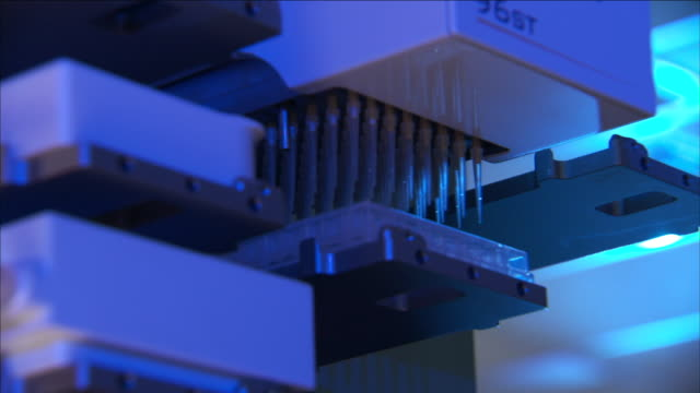 automated pipettes fill a tray in a lab. - pipette stock videos & royalty-free footage