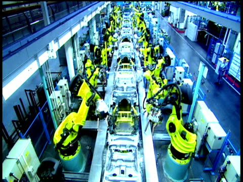 Automated production line robots punch rivet and weld skeletal car chassis Bremen