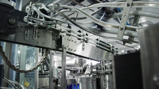 vídeos de stock e filmes b-roll de automatic canning machine transports aluminum cans with a conveyor belt in an indoor manufacturing facility - automatizado