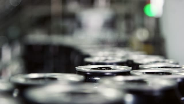 automatic canning machine transports aluminum cans with a conveyor belt in an indoor manufacturing facility - aluminium stock videos & royalty-free footage