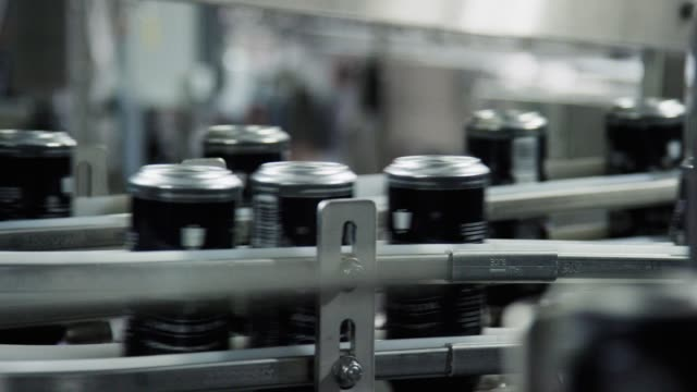 automatic canning machine transports aluminum cans with a conveyor belt in an indoor manufacturing facility - industrial equipment stock videos & royalty-free footage