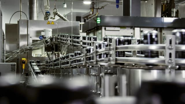 vídeos de stock e filmes b-roll de automatic canning machine transports aluminum cans with a conveyor belt in an indoor manufacturing facility - beer alcohol