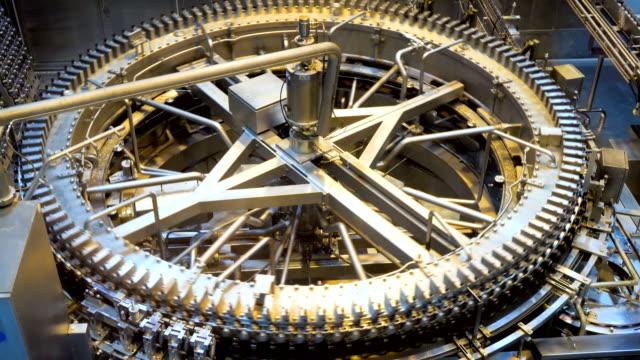 automatische konservenmaschine transportiert aluminiumdosen mit einem förderband in einer fertigungsanlage. - effektivität stock-videos und b-roll-filmmaterial
