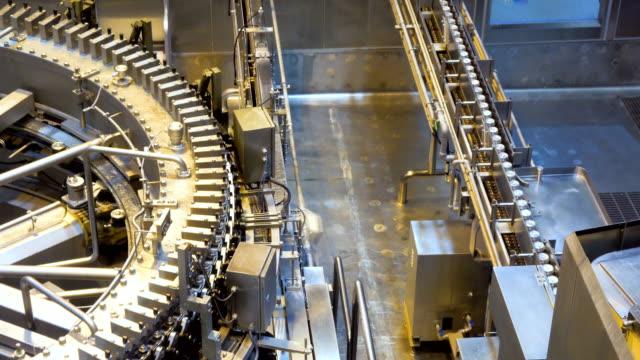 automatische konservenmaschine transportiert aluminiumdosen mit einem förderband in einer fertigungsanlage. - abfüllanlage stock-videos und b-roll-filmmaterial