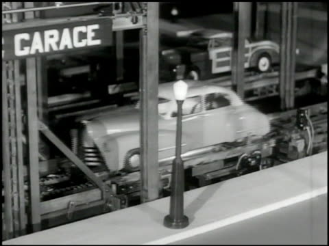 automatic garage model w/ model cars demonstrating car entering garage, sliding on platform, taking elevator up, clamp picking up car, lifting into... - schraubstock stock-videos und b-roll-filmmaterial