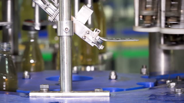 automatic machine putting the metal cap on glass bottle - bottle cap stock videos & royalty-free footage