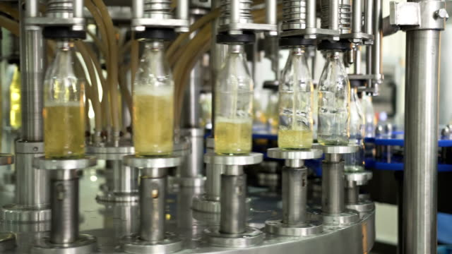 automatic machine working all time for filling the herb beverage into glass transparent bottle - production line stock videos & royalty-free footage
