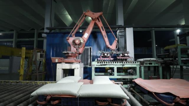 vídeos de stock, filmes e b-roll de manipulador automático na oficina da fábrica - produto interno bruto