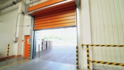 automatic roller gates of orange color are lowering down in the warehouse of woodworking plant.