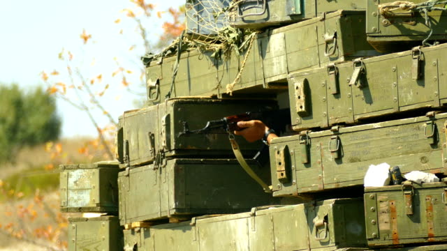 automatic shooting through a protective barricade of boxes - barracks stock videos & royalty-free footage