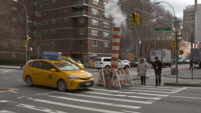 Automobile and pedestrian traffic on New York City street. Pedestrians use crosswalk passing by steam stack.