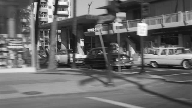 stockvideo's en b-roll-footage met ms pov automobile moving near kalakaua avenue past hotels at honolulu hawaii - 1959