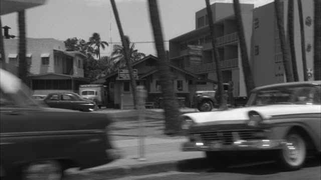 ms pov automobile passing shops and hotels in waikiki area kuhio beach at honolulu hawaii - anno 1959 video stock e b–roll