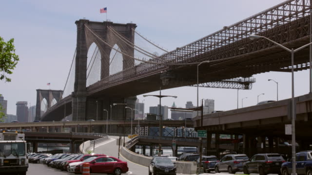 Automobile traffic moving under, on top of, and around the Brooklyn Bridge.