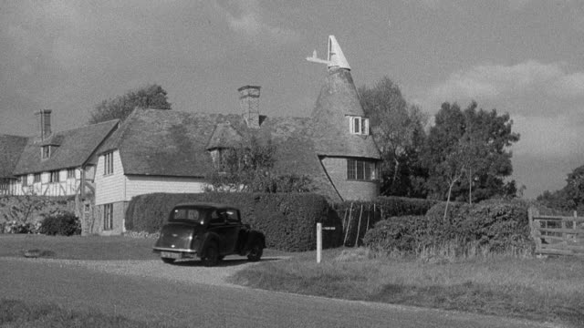 1952 MONTAGE Automobile traveling country lane, passing a dog at doghouse, arriving at rural residence with flock of chickens in side yard / Wadhurst, England, United Kingdom