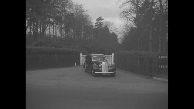 automobiles exit and enter gates of fort belvedere the home of edward viii / gathered reporters / eric mieville secretary to albert duke of york in... - サリー州点の映像素材/bロール