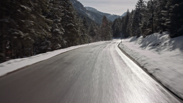 automotive background / process plate of the driver POV (point of view), while driving on a Bavarian rural road in the alpine upland in winter on a nice sunny day  / on board - rigged camera shot