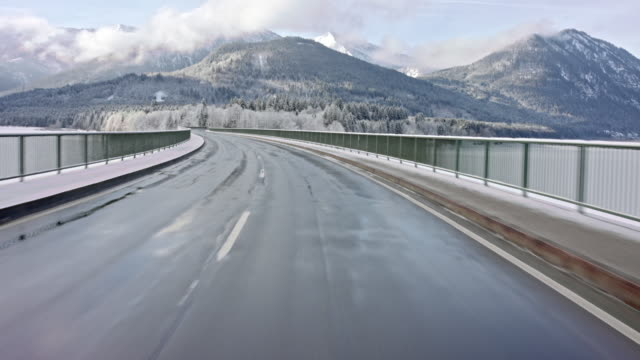automotive background / process plate of the drivers POV (point of view), while driving on a Bavarian road in the alps in winter on a sunny day  / on board - rigged camera shot