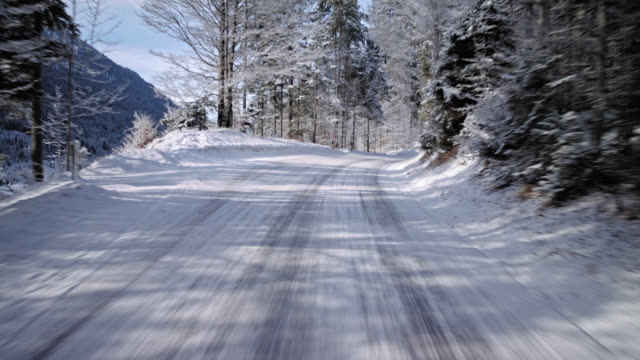 automotive background / process plate of the drivers POV (point of view), while driving on a Bavarian rural road in the alps in winter on a nice sunny day  / on board - rigged camera shot