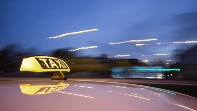 vidéos et rushes de automotive on board a car long exposure time lapse rigging shot of a german taxi. taxi roof sign in foreground. streaking reflections in the roofs surface of the yellow cab. the background is motion blurred and city lights are streaking. - yellow taxi