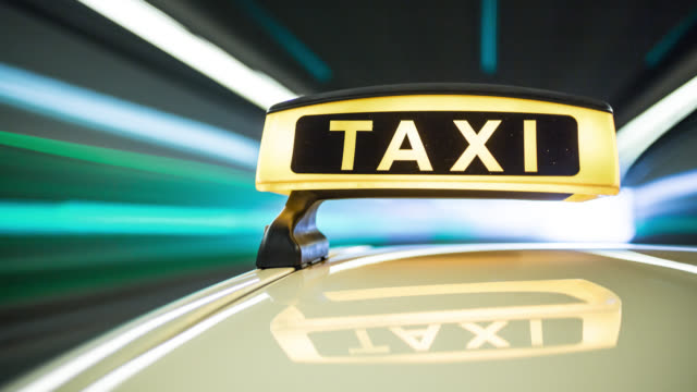 Automotive on board a car long exposure time lapse rigging shot of a german Taxi. Taxi roof sign / Dachzeichen in foreground. Taxi sign reflects in the roofs surface of the yellow cab. The background is blurred.