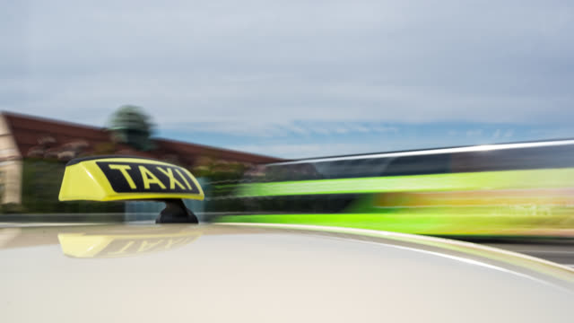 vidéos et rushes de automotive on board a car long exposure time lapse rigging shot of a german taxi. taxi roof sign / dachzeichen in foreground. taxi sign reflects in the roofs surface of the yellow cab. the city background is blurred. - yellow taxi