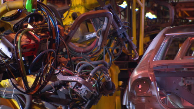 automotive robots weld a car on an assembly line as sparks fly. - michigan stock videos & royalty-free footage
