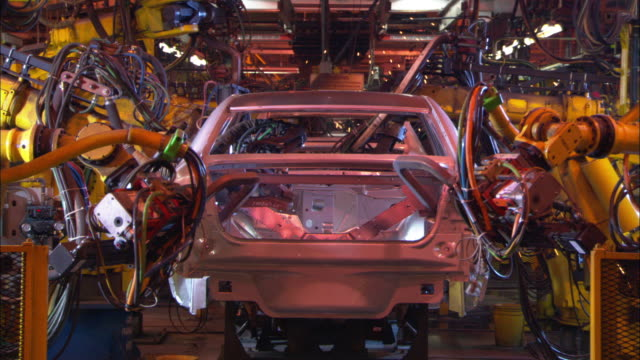 Automotive robots weld a car on an assembly line as sparks fly.