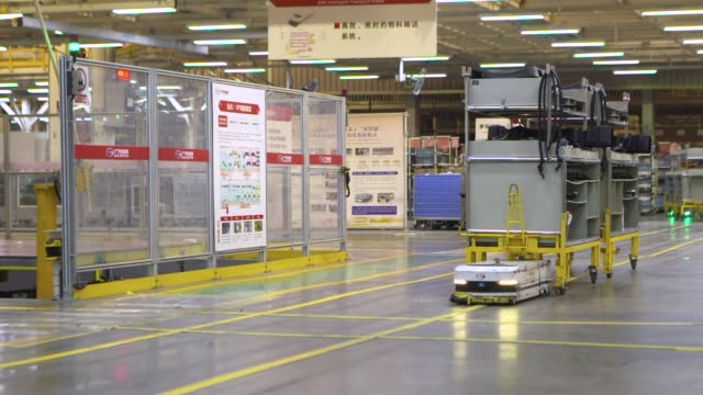 Autonomous transport robots move shelves with parts through the Guangzhou Automobile Group Co Ltd's plant in Guangzhou China on Thursday Nov 2 2017