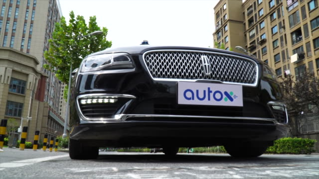 autox driverless taxi service operating in shanghai, drives towards camera - taxi stock videos & royalty-free footage
