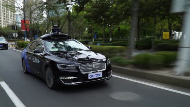 autox robo taxi, a driverless taxi service, driving on streets of shanghai - taxi stock videos & royalty-free footage